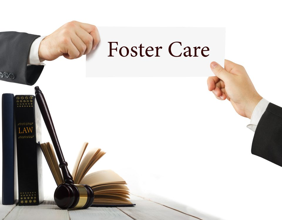 Law book and wooden judges gavel on table in a courtroom or law enforcement office. Lawyer Hands holding business card with text Foster Care